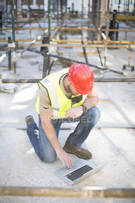 Travailleur de la construction utilisant une tablette sur le chantier — Photo de stock