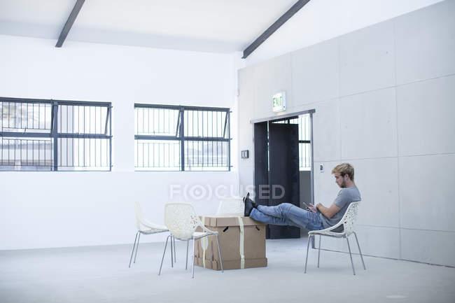 Uomo ufficio creativo rilassante su una sedia e scatole — Foto stock