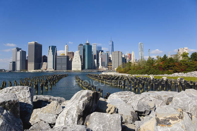 USA, New York, Lower Manhattan skyline skyscrapers and East River seen from Brooklyn Bridge Park — Stock Photo