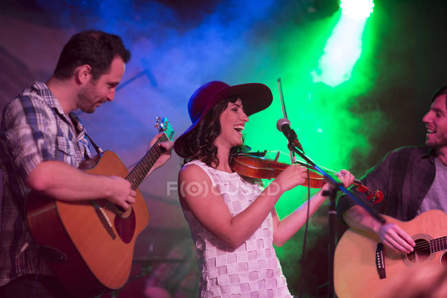 Folk band with violin and two acoustic guitars in club — Stock Photo