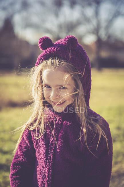 Портрет улыбающейся маленькой девочки в фиолетовой куртке в капюшоне — стоковое фото