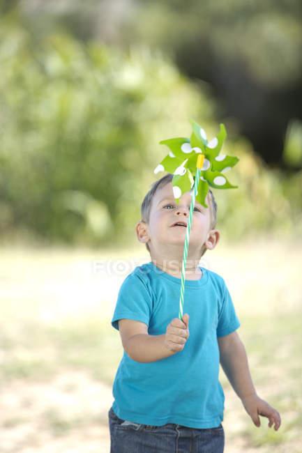 Ragazzino all'aperto che gioca con mulino a vento di carta — Foto stock