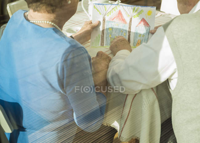 Senior couple watching child's drawing — Stock Photo