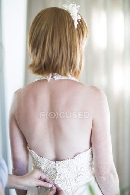 Bridesmaid buttoning up brides wedding dress — Stock Photo