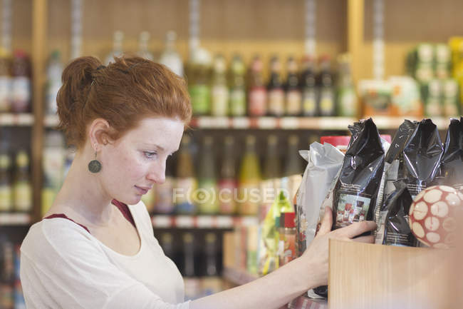 Female shop assistant sorting merchandise in wholefood shop — Stock Photo