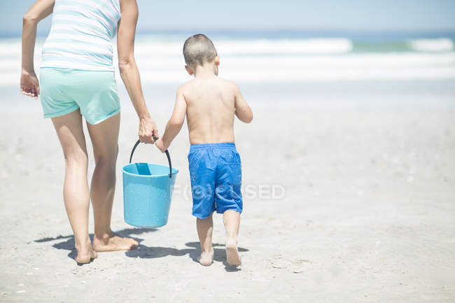 Mother and son on beach walking with a bucket — Stock Photo