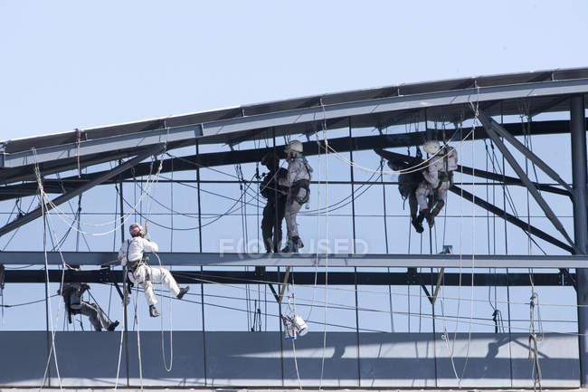 Uomini che lavorano a fianco dell'edificio — Foto stock