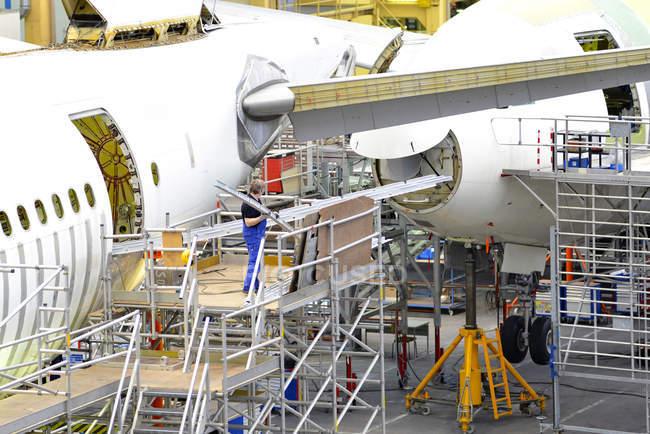 Люди, работающие на строительстве самолетов — стоковое фото