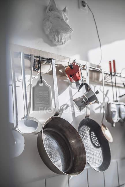Sartenes y otros utensilios colgados en la pared de la cocina - foto de stock
