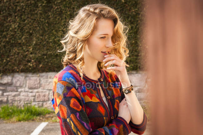 Young woman with curly hair wearing patterned cardigan — Stock Photo