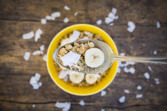 Ложка гранола, банан фрагмента та кокосового пластівці — стокове фото