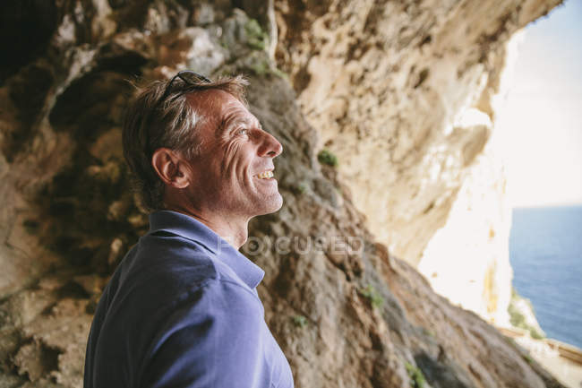 Man standing inside a cave looking at view — Stock Photo