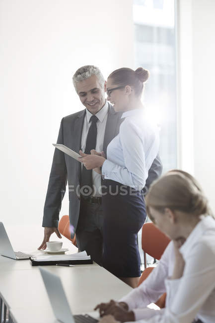 Manager and assistant sharing digital tablet in office — Stock Photo