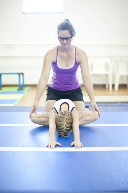 Coach with girl doing gymnastics exercise on floor — Stock Photo