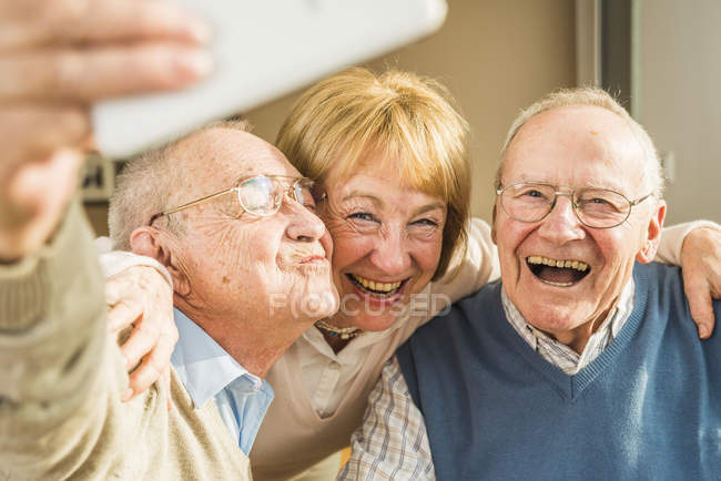 Cheerful seniors taking selfie with smartphone — Stock Photo
