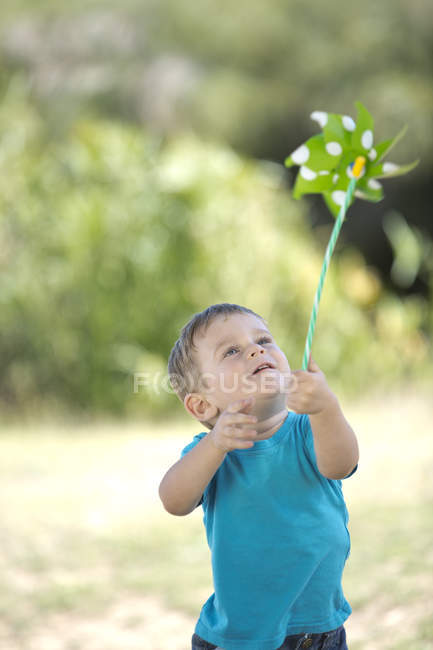 Little boy outdoors playing with paper windmill — Stock Photo