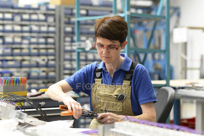 Worker assembling cables in a switchboard construction factory — Stock Photo
