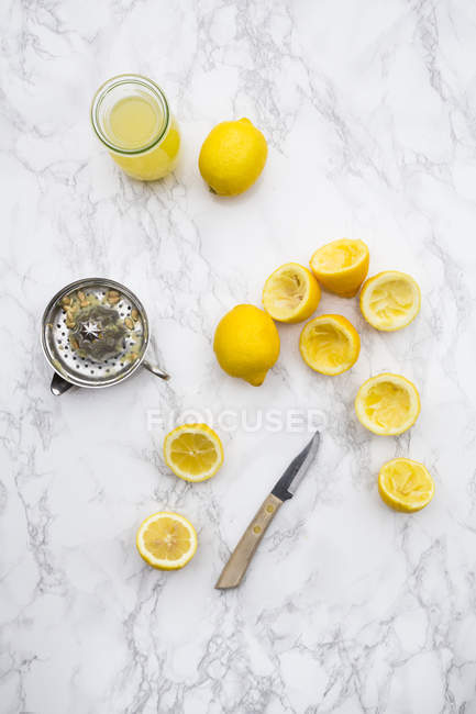 Le jus de citron fraîchement pressé, citrons biologiques et presse-citron — Photo de stock