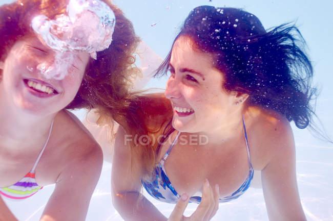 Amigas nadando na piscina subaquática — Fotografia de Stock