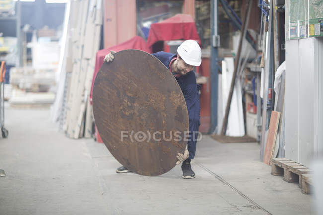 Worker in factory with metal plate — Stock Photo