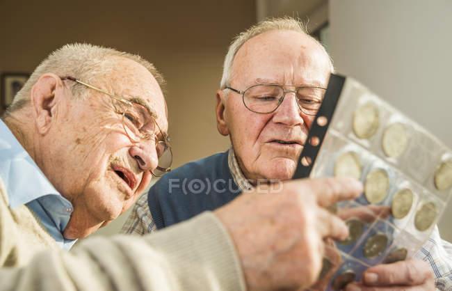 Deux amis seniors avec un album de pièces à la maison — Photo de stock