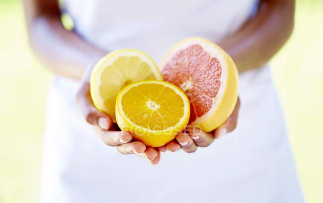 Женские руки, держа половинки апельсина и грейпфрута — стоковое фото