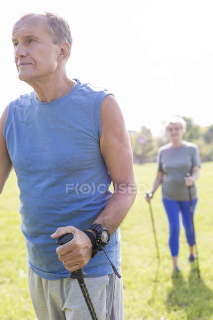 Старший пара робити нордичної ходьби у парку — стокове фото