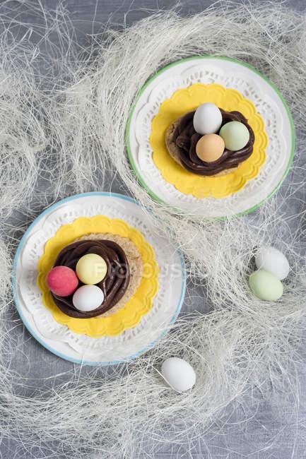Kekse mit Schokoladenganache und gezuckerten Mandeln in Form eines Osterkorbs — Stockfoto