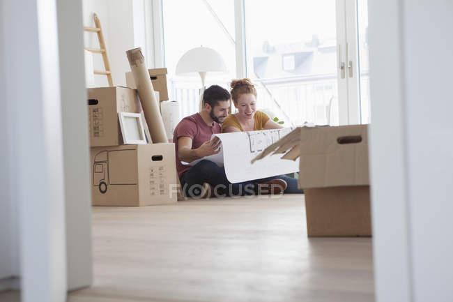 Jeune couple dans le nouvel appartement avec des boîtes en carton, tenant le plan au sol — Photo de stock