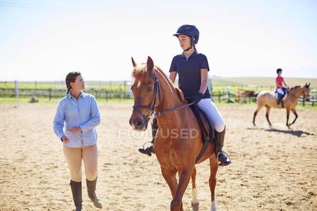Coach and girl on horse on riding ring — Stock Photo