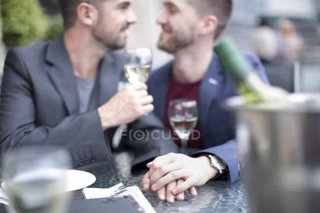 Гей пара обмена интимный момент в ресторане — стоковое фото
