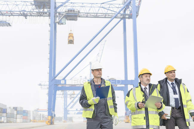 Three men wearing protective clothing at container port — Stock Photo
