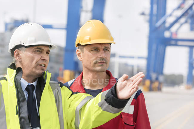 Two men in protective clothing talking at container port — Stock Photo