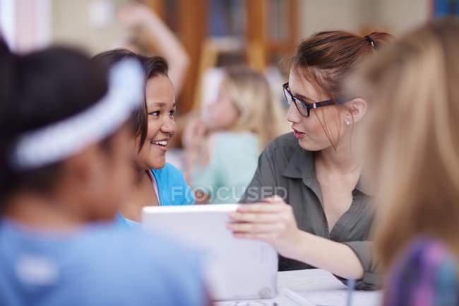 Profesor y sonriendo colegialas con tableta digital - foto de stock