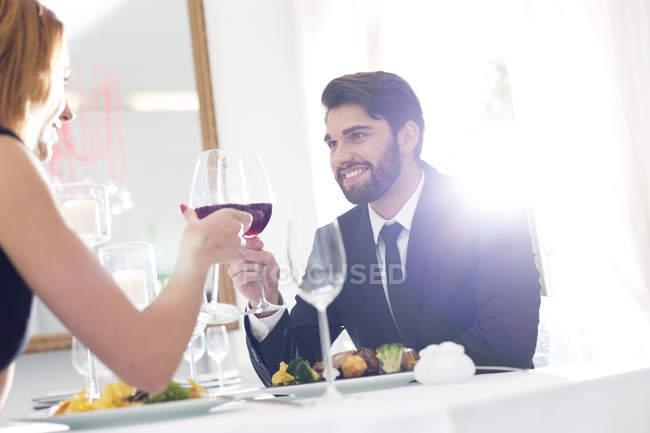 Elegant couple toasting wine glasses in restaurant — Stock Photo