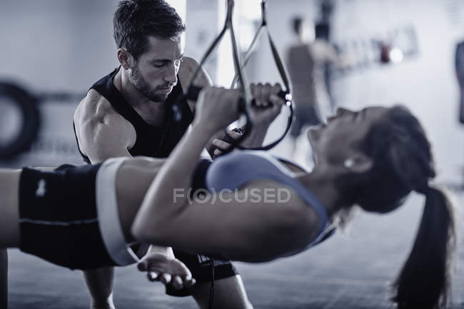 Fitness trainer keeping time with woman doing pull-ups — Stock Photo