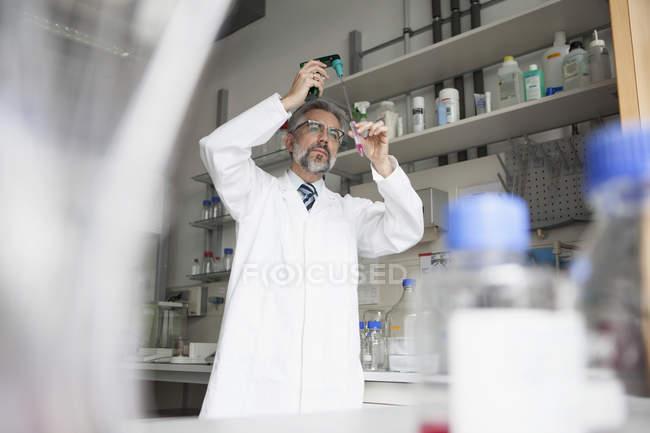 Scientist pouring liquid in test tube — Stock Photo