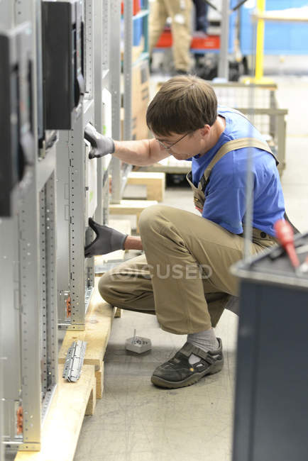 Worker in a switchboard construction factory — Stock Photo