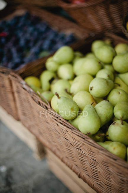 Fresh pears for sale in wicker basket at farmer market — Stock Photo