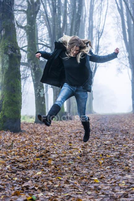 Жінка, стрибки в повітря на лісових відстежувати — стокове фото