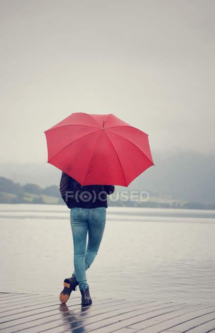 Австрія, Мондзю, Дівчинка-підліток з червоним парасолька стояти під Лейкшор — стокове фото