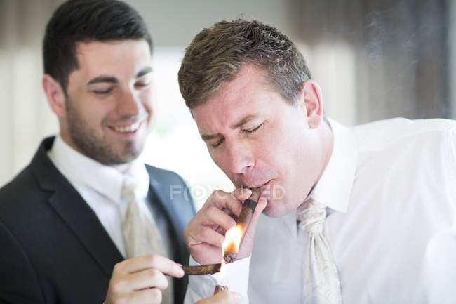 Groom smoking a cigar with best man before wedding — Stock Photo
