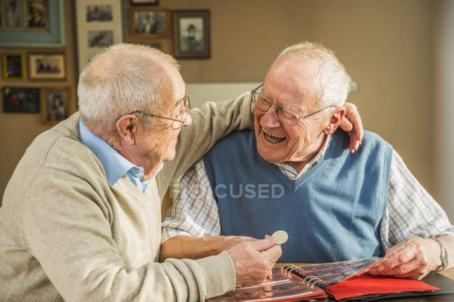 Two happy senior friends with coin album laughing at home — Stock Photo