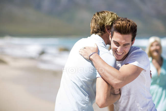 Friends embracing on beach — Stock Photo