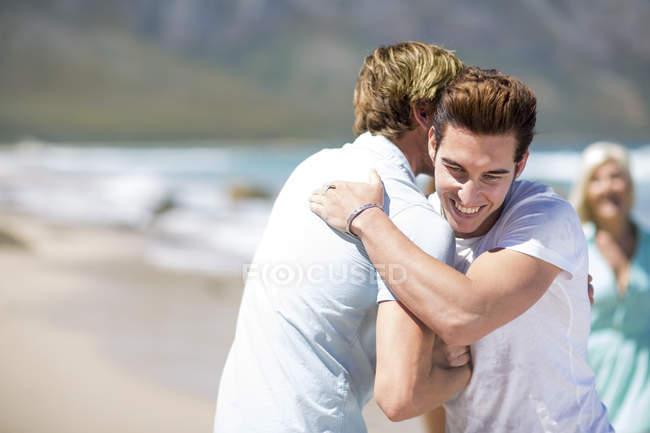 Друзі обіймаються на пляжі — стокове фото