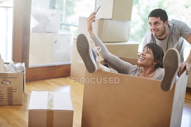 Casa móvil par juguetón sentado en una caja teniendo un selfie - foto de stock