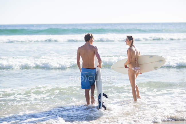 Young couple with their surfboards at the sea — Stock Photo