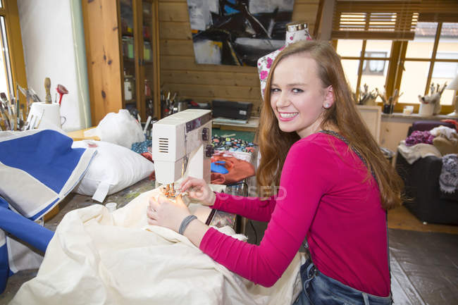 Portrait of smiling female teenager using sewing machine in a workshop — Stock Photo