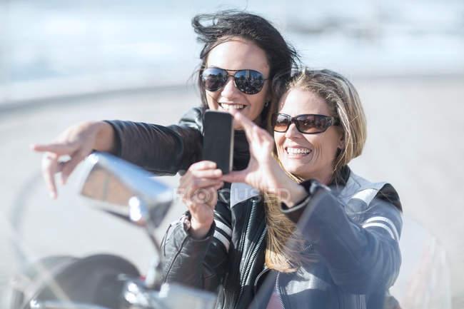 Две женщины на мотоцикле делают селфи — стоковое фото