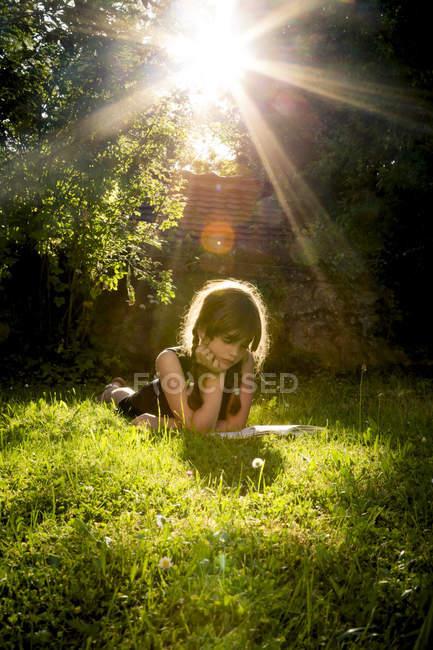 Девочка лежит на лугу и читает книгу. — стоковое фото